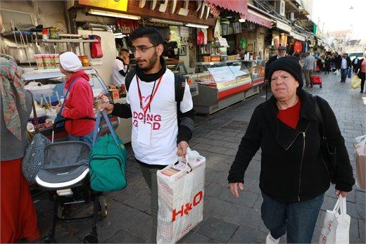 מתנדבים סוחבים סלים בשוק מחנה יהודה | צילום: אלי דסה